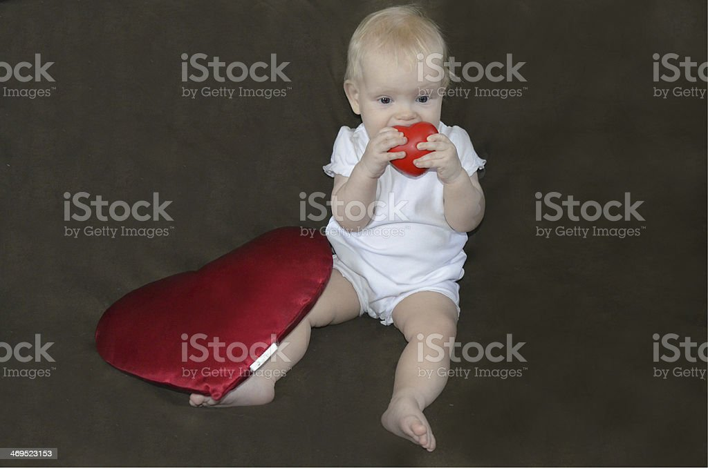 Little baby playing with a red heart on a brown background royalty-free stock photo
