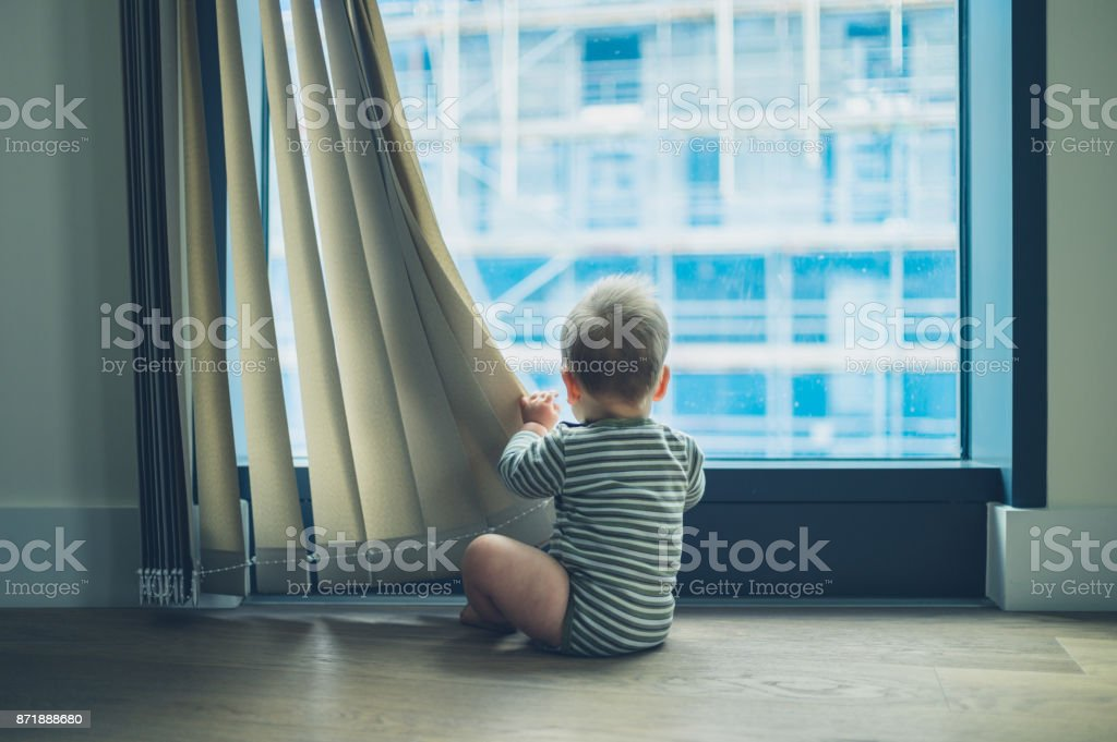 LIttle baby playing with curtain in apartment stock photo
