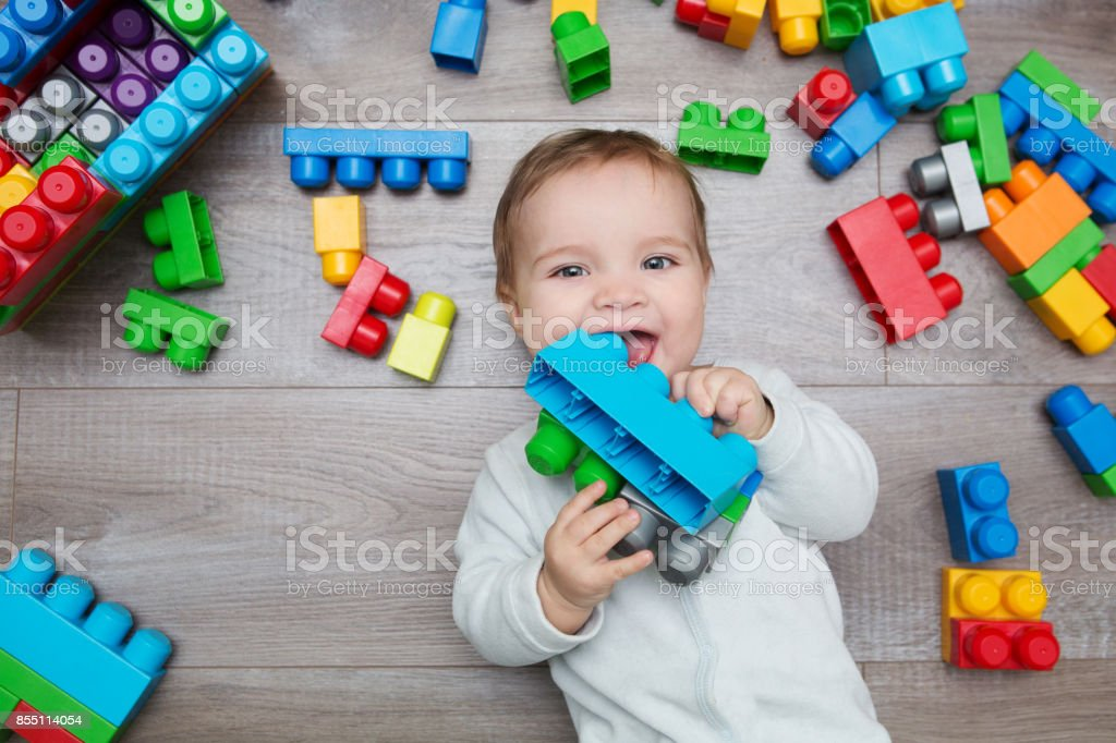 Little baby playing with lots of colorful plastic blocks constructor on floor in the room. stock photo