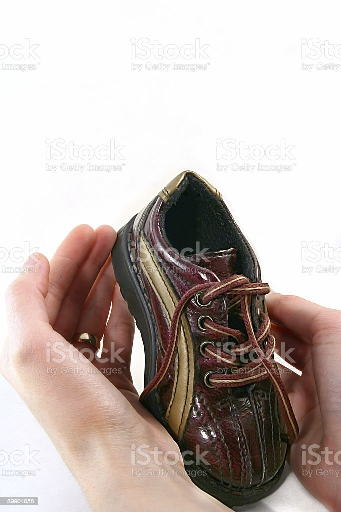 little baby shoe and parents hands royalty-free stock photo