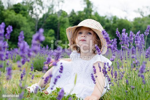 little baby girl sitting in the middle of the lavender plantation with hat and looking up