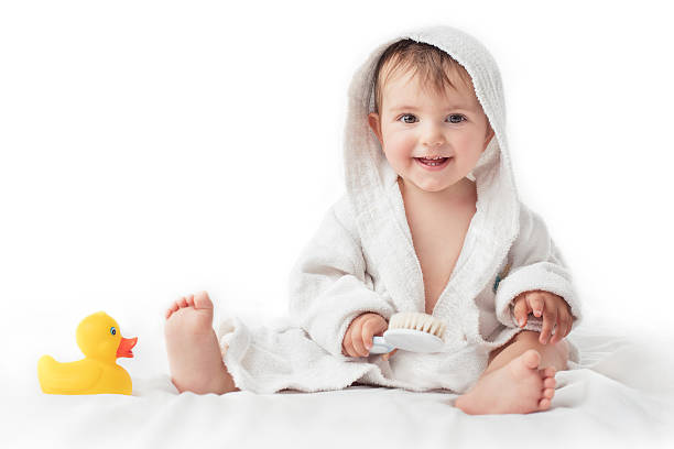Little baby smiling under a white towel, bath time concept stock photo