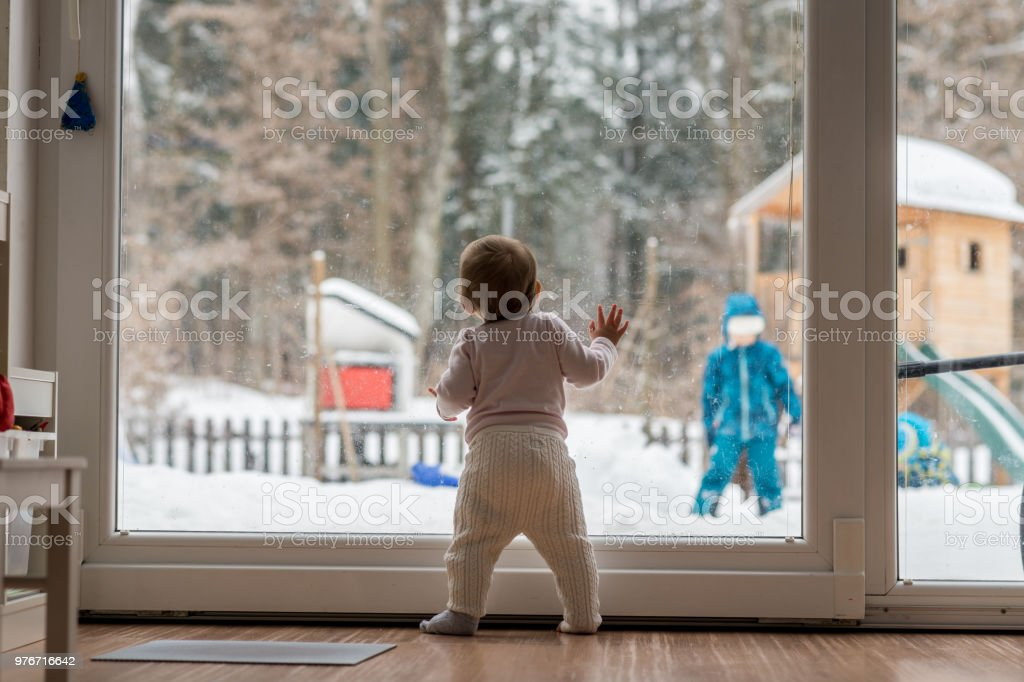 Little baby standing watching a sibling outdoors stock photo