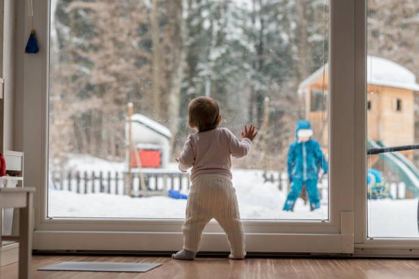wenig baby stehend beobachtete ein geschwister im freien - schneespiele stock-fotos und bilder