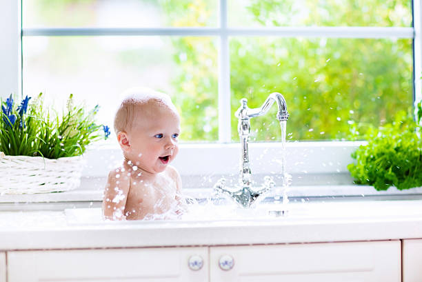 kleines baby mit bad - kinderbadewanne stock-fotos und bilder