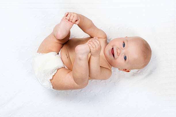 Little baby wearing a diaper playing on white knitted blanket stock photo
