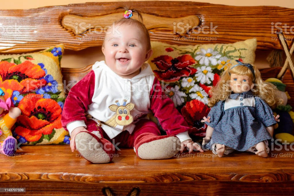 Little charming baby with a tail sits on a sofa with embroidered...