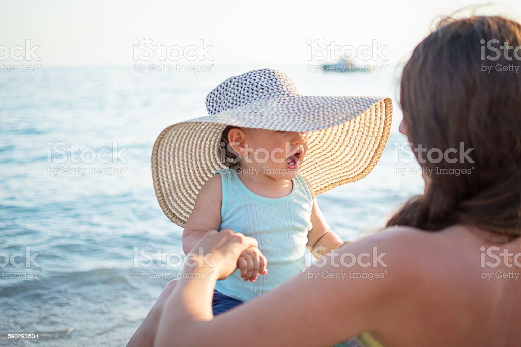 Little baby with straw hat and mom on beach royaltyfri bildbanksbilder