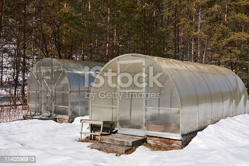 Little back yard home greenhouse in the snow. Two greenhouses in spring sunny clear day