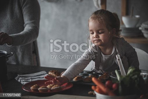 Shot of cute toddler girl standing over kitchen counter and taking out muffins out of the muffin tray and putting them on the plate while her mother is standing next to her and cooking lunch.