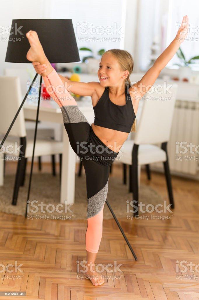Little ballerina exercising at home - standing on one leg