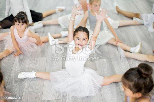 istock Little ballerina girls stretching in studio 1005966790