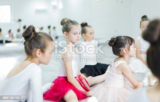 905560090 istock photo Little ballerina girls stretching in studio 988765700