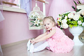 A little ballerina in a dress sits in a dance class on the floor. Near a bouquet of flowers.