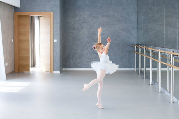 Little ballerina is dancing in ballet class. Cute child girl is wearing in white ballet shoes, clothes and dress with tutu skirt. Kid in classical dance school for children. stock photo