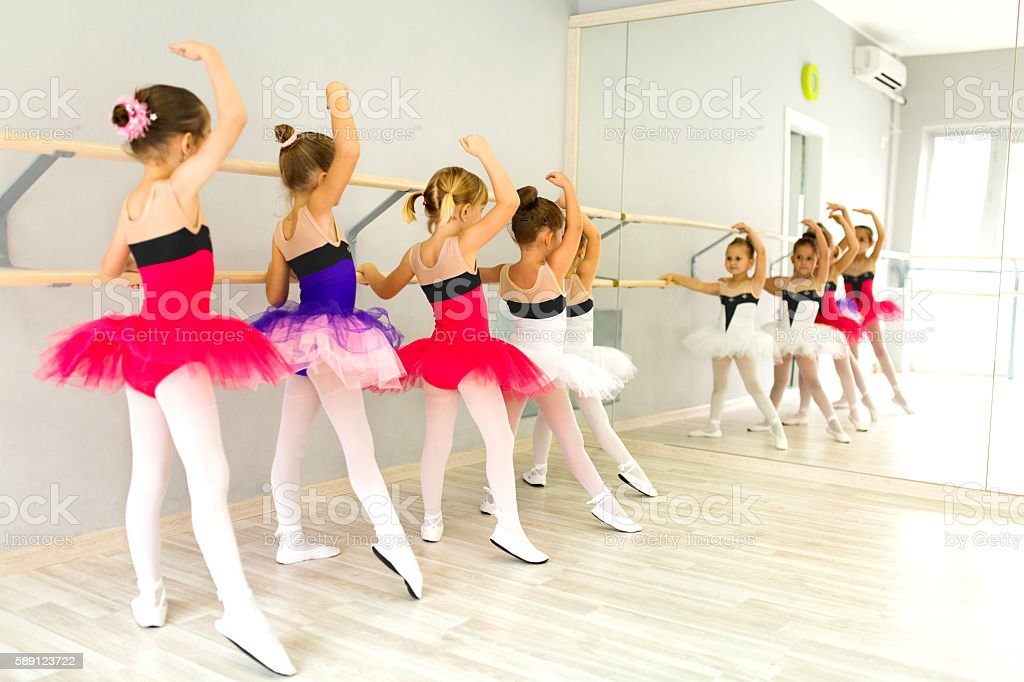 Little ballerinas in tutu using barre and practicing postures. stock photo