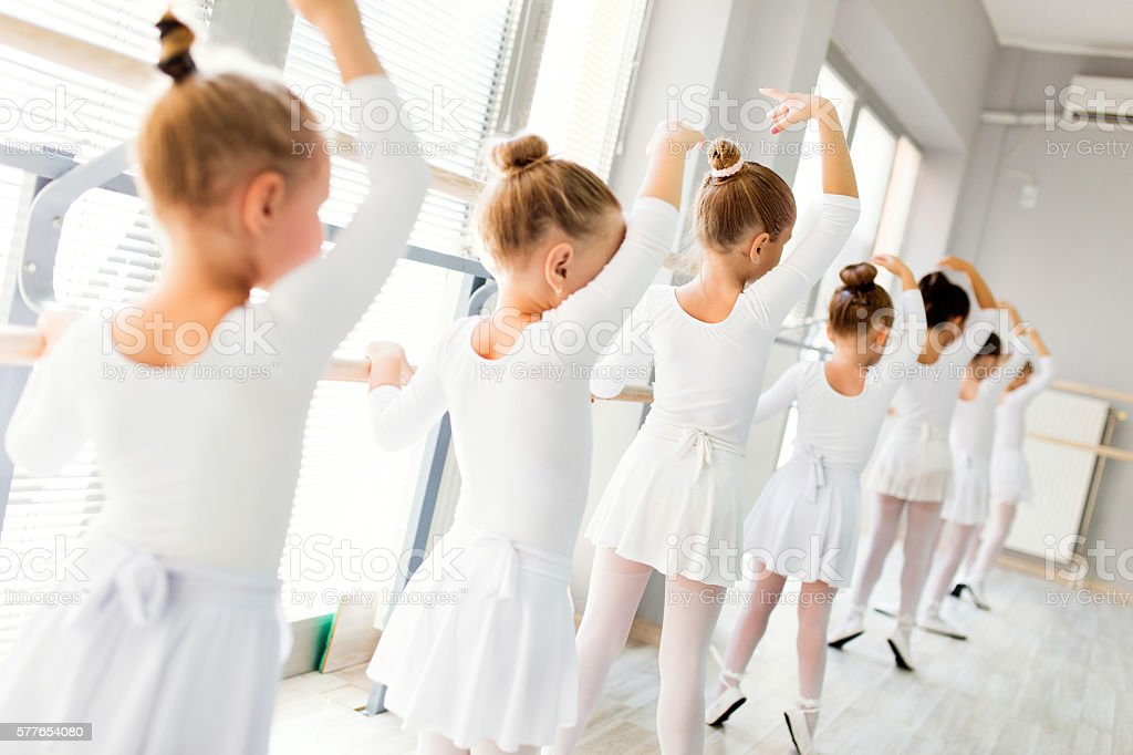 Little ballerinas using barre while practicing in dance studio. - Photo