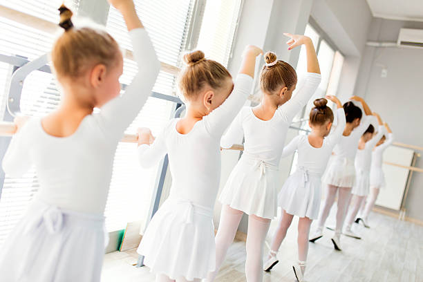 Little ballerinas using barre while practicing in dance studio. stock photo