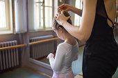 Lovely ballet mother making a hairstyle for her beautiful daughter.