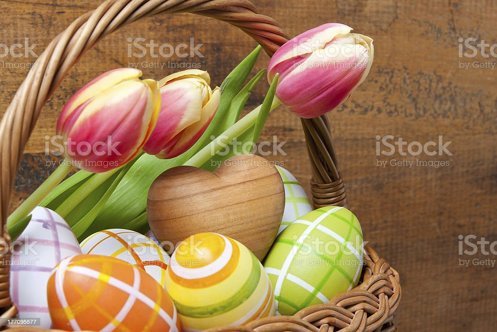 Little basket with easter eggs and tulips royalty-free stock photo