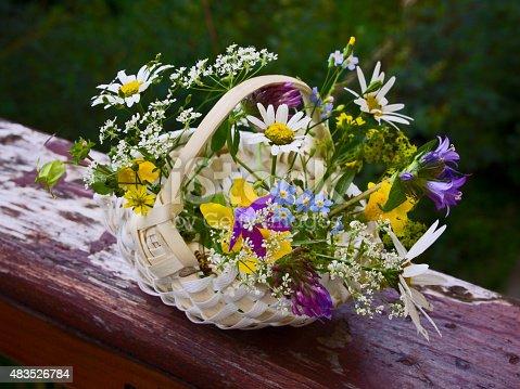 OLYMPUS DIGITAL CAMERA Little handmade basket with wild multicolored flowers.