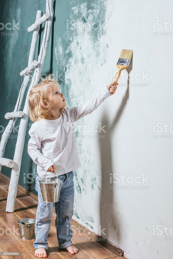 Little beautiful and happy child in jeans paint the wall - foto de stock