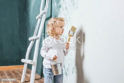 istock Little beautiful and happy child in jeans paint the wall 625063880