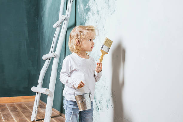 little beautiful and happy child in jeans paint the wall - bild wandtreppe stock-fotos und bilder