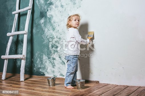 istock Little beautiful and happy child in jeans paint the wall 625064122