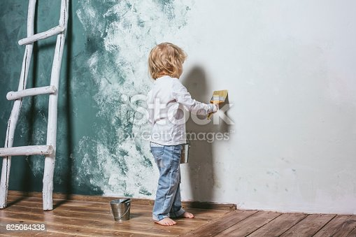 istock Little beautiful and happy child in jeans paint the wall 625064338