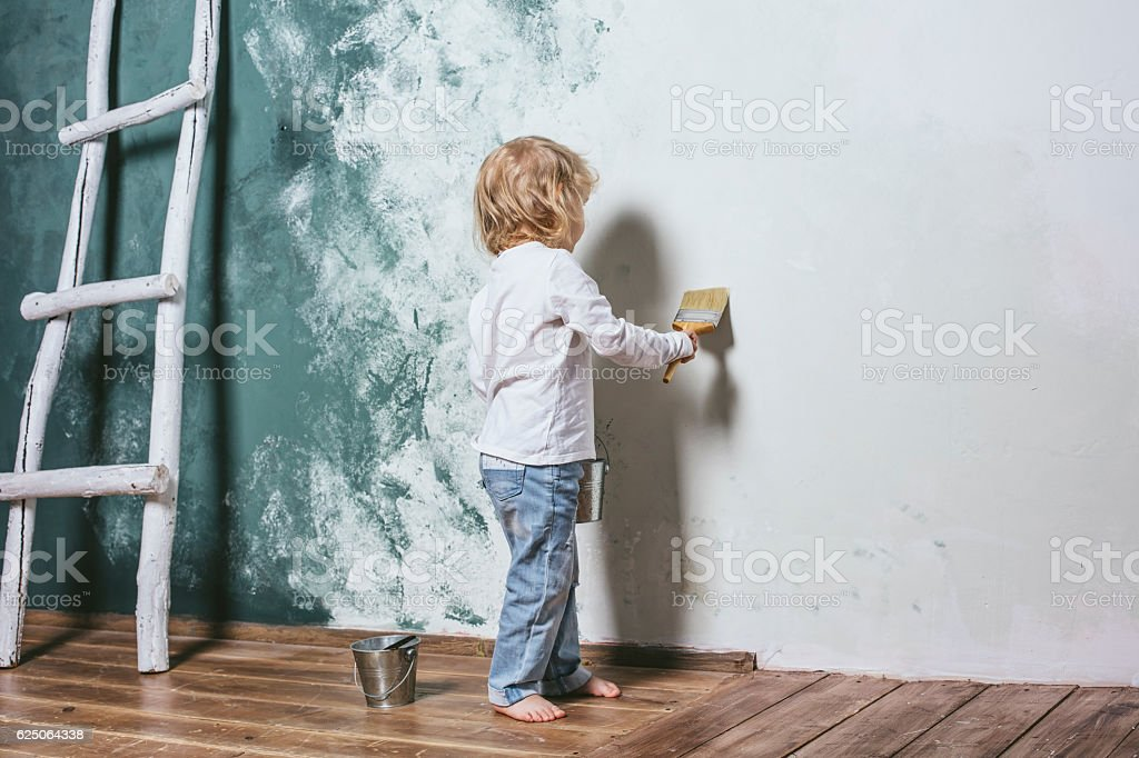 Little beautiful and happy child in jeans paint the wall – Foto