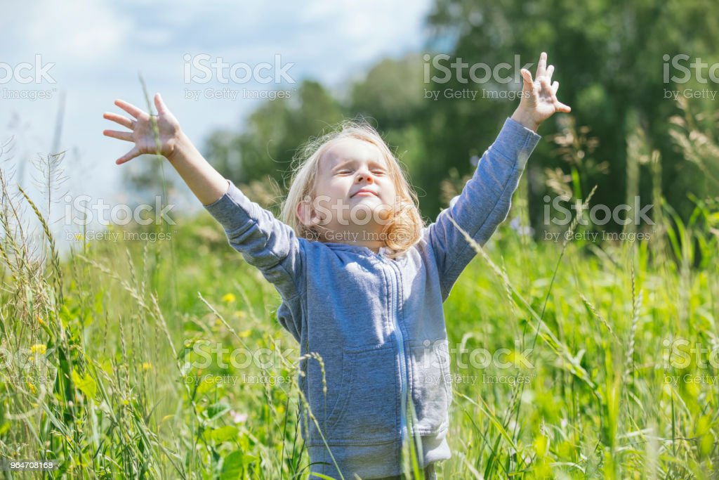 Little beautiful baby girl outdoors in a field in the fresh air happy royalty-free stock photo