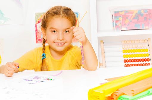 istock Little beautiful blond girl puts beads on string 529356391