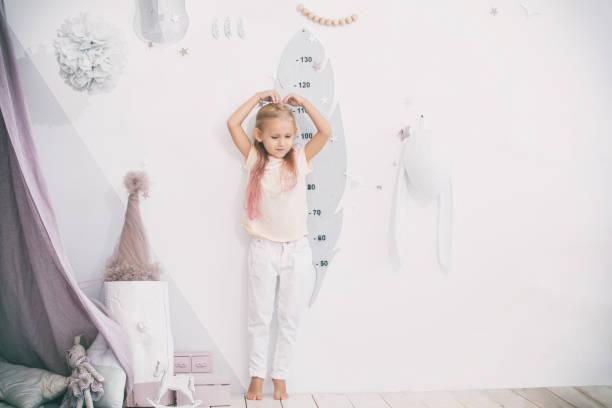 kleines schönes kind mädchen im kinderspielzimmer misst ihre höhe - wachstumstabelle baby stock-fotos und bilder