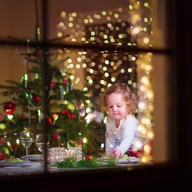 kleine schöne mädchen im weihnachts-abendessen - kinderzimmer tischleuchten stock-fotos und bilder