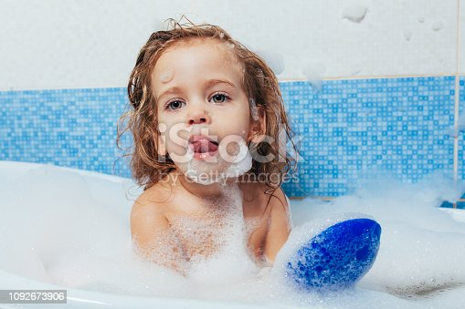 520441939 istock photo Little beautiful girl bathes in a bathroom, plays the fool and shows tongue. Fun bathing children. Positive hygiene. Independent child 1092673906