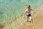 istock little beautiful girl walks along the beach by the sea on a 1277742719