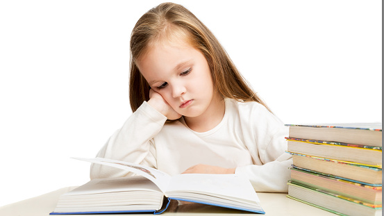 little beautiful preschooler girl sitting at the table reads books, tired and sad on a white background.childhood