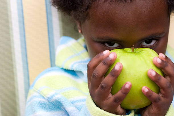 Little beauty peeks from behind apple stock photo