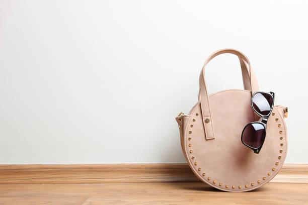 little beige round female handbag and sunglasses stock photo