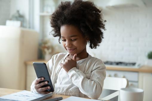 Little biracial girl watch online class on cellphone