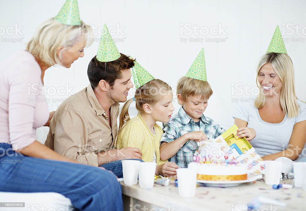 Little birthday boy opening gift given by his family royalty-free stock photo