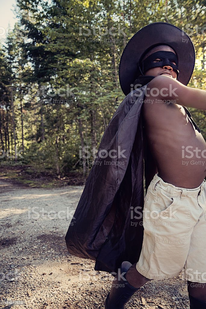 Little black boy costumed as Zorro playing outside. stock photo