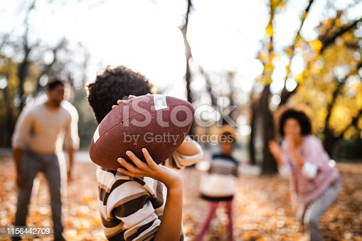 Small African American boy and his family playing rugby in autumn day at the park. Focus is on ball and hands.