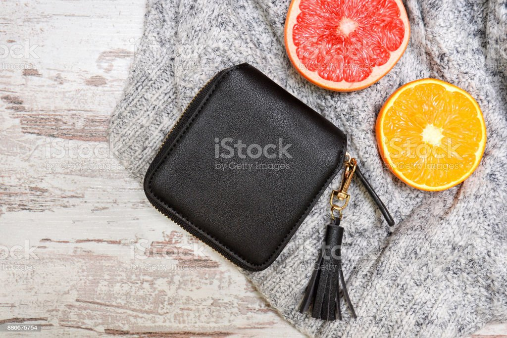 Little black female purse, and citrus on a sweater. Fashionable concept. stock photo