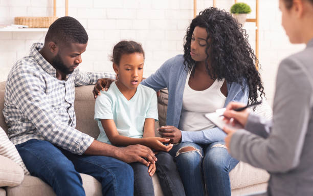 Little black girl and her parents at psychologist consultation Bipolar Disorder In Children Concept. Little african american girl and her parents at reception of psychologist, kid sharing her feelings with doctor counseling stock pictures, royalty-free photos & images