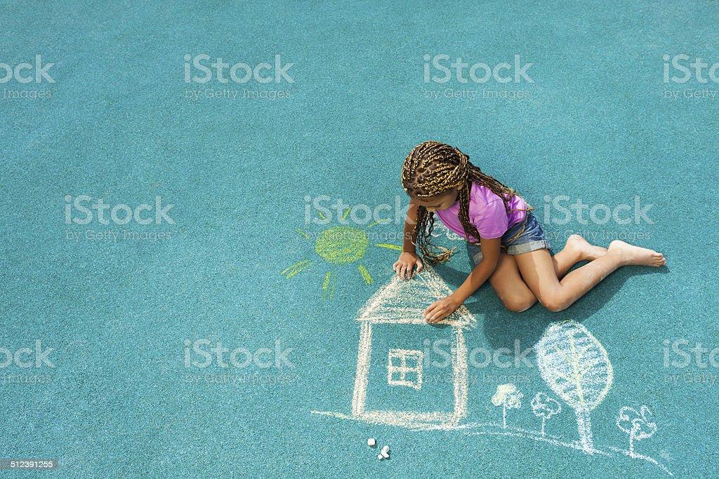 Little black girl drawing chalk house image stock photo