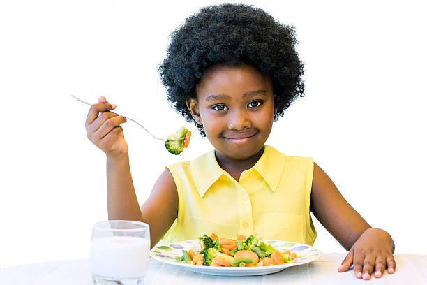 Little black girl eating healthy vegetable meal. stock photo