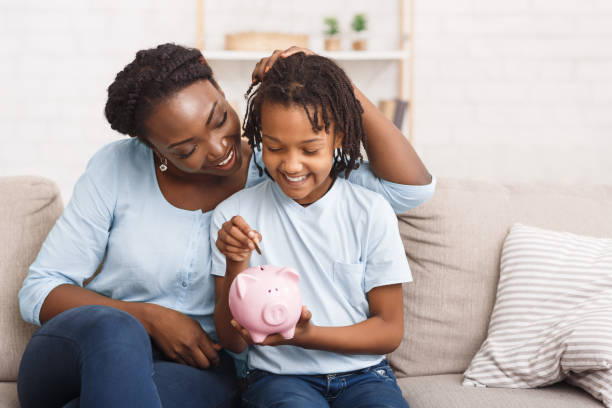 Little black girl putting money to piggy bank African Mother And Daughter Putting Coins Into Piggy Bank At Home. Free space miserly stock pictures, royalty-free photos & images