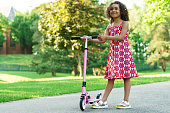 Cute and little black girl with a kick scooter in a city park